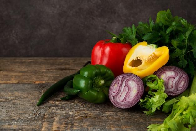 素朴な木製のコピースペースに新鮮な有機野菜とハーブ