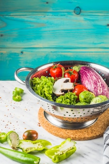 Fresh organic vegetables in colander over marble tabletop