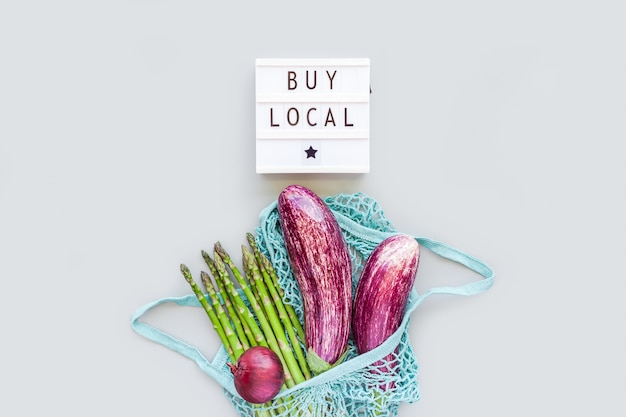 Fresh organic vegetables in eco cotton mesh shopping bag with text buy local on lightbox flat lay, top view with copy space on gray background. sustainable lifestyle. zero waste, plastic free concept.