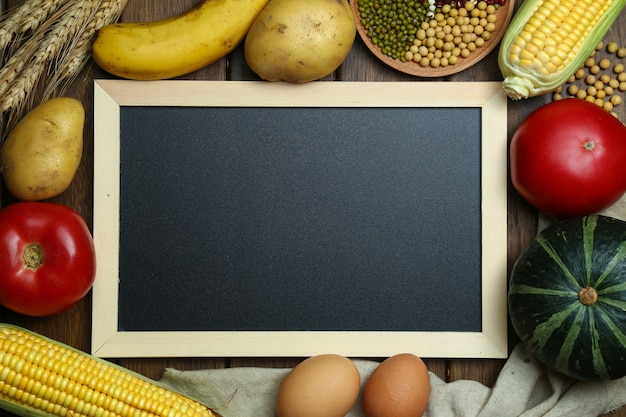 빈티지 나무 테이블에 칠판과 신선한 유기농 야채, 과일, 계란, 콩, 옥수수