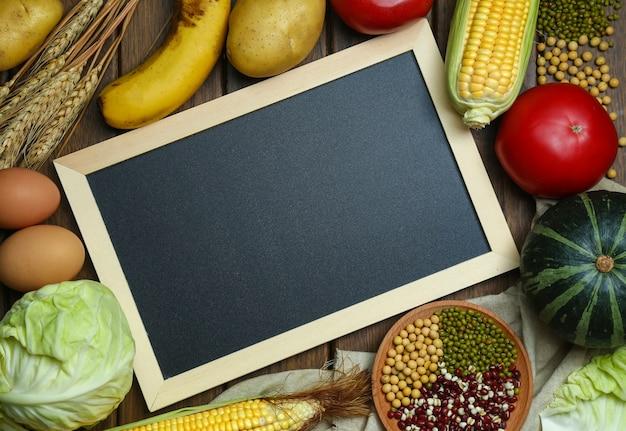 ヴィンテージ木製テーブル上に黒板と新鮮な有機野菜、果物、卵、豆、およびコーン