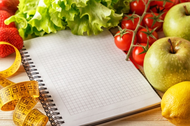 Fresh organic vegetables and fruits near open blank notebook