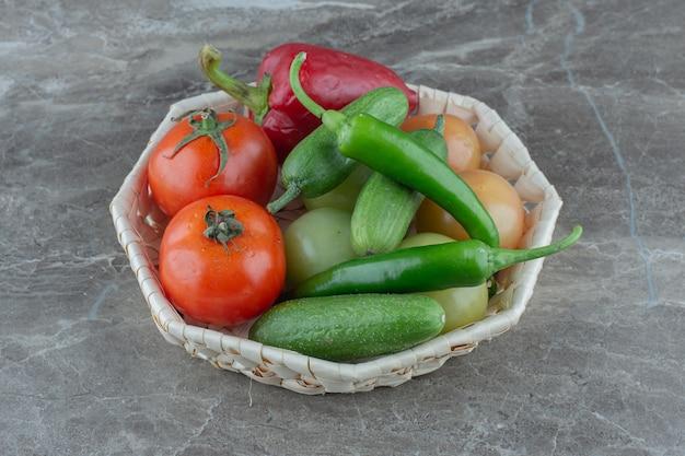 회색 표면 위에 바구니에 든 신선한 유기농 야채