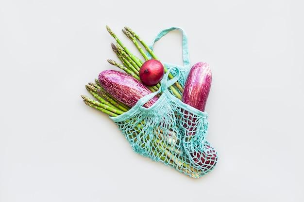 青いエコ再利用可能な綿メッシュショッピングバッグの新鮮な有機野菜フラットレイ、上面図