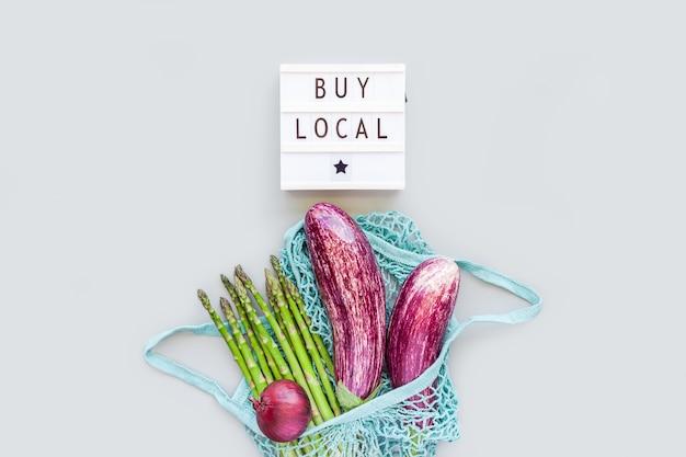 Свежие органические овощи в хозяйственной сумке из сетки из эко-хлопка с текстом buy local на плоской планировке лайтбокса, вид сверху с копией пространства на сером фоне. устойчивый образ жизни. нулевые отходы, концепция без пластика.