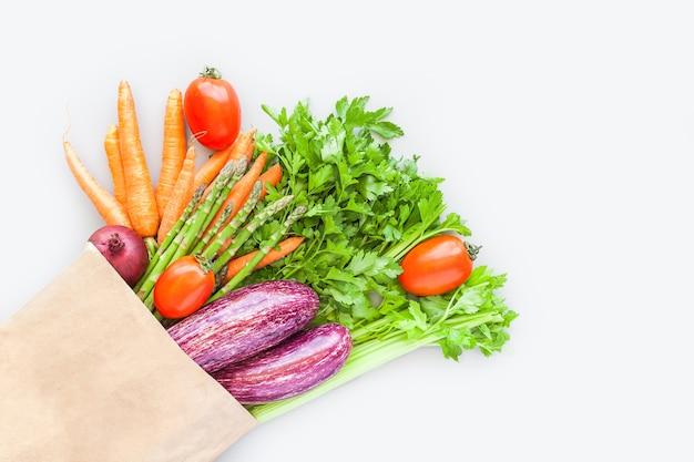 フラットレイのエコクラフト紙ショッピングバッグの新鮮な有機野菜、灰色の背景にコピースペースと上面図。持続可能なライフスタイル。ゼロウェイスト、プラスチックフリー、ケアパッケージ、寄付のコンセプト