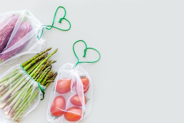 Свежие органические овощи в экологически чистых многоразовых сумках для покупок, плоская планировка, вид сверху