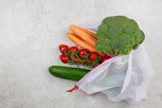 再利用可能なテキスタイルショッピングバッグに入った新鮮な有機野菜。ゼロウェイストと環境にやさしいコンセプト。