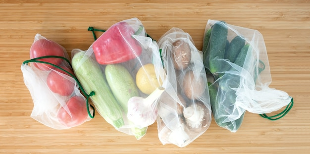 Fresh organic vegetables mushrooms in zero waste shopping bag on wooden table background flat lay