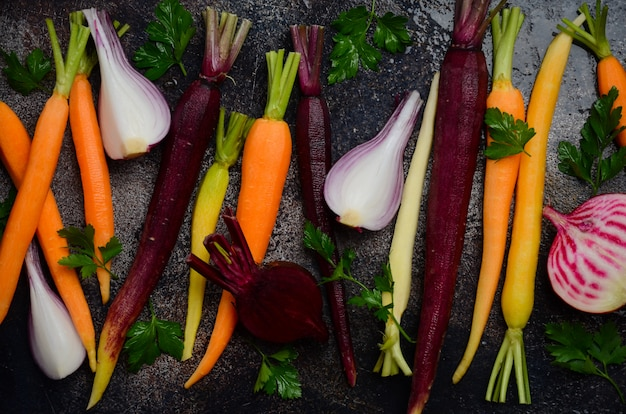 Fresh organic vegetables on old rusty baking sheet, ready for cooking, top view.