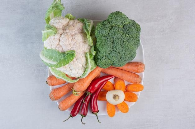 하얀 접시에 신선한 유기농 야채입니다. 고품질 사진