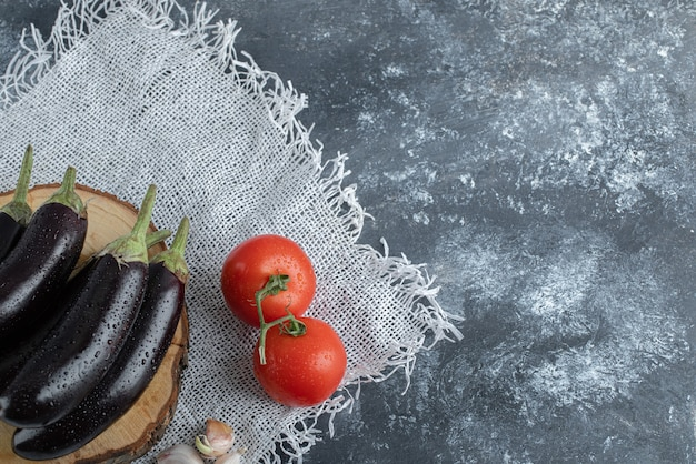 Verdure biologiche fresche. melanzane viola su tavola di legno con pomodoro e aglio