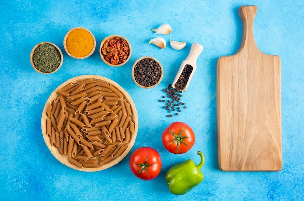 生パスタとスパイスを使った新鮮な有機野菜。青い背景の上の木の板。
