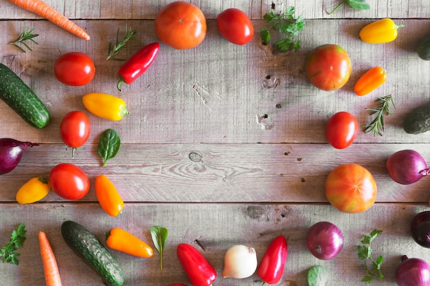 Fresh organic vegetables on a wooden background. top view
