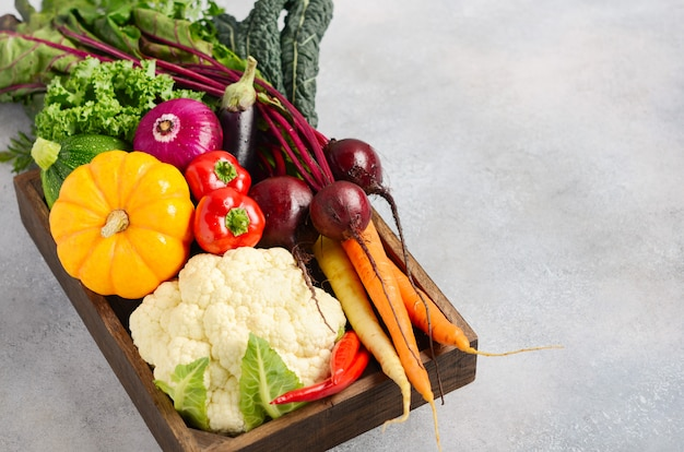 Fresh organic vegetables in wooden box on gray concrete background.