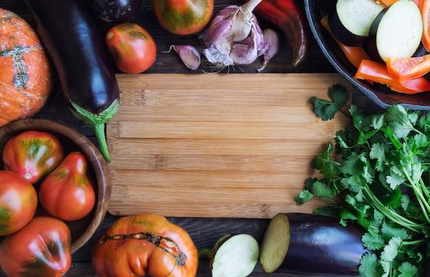 テキスト用のスペースと素朴な木製の背景に新鮮な有機野菜。上面図。