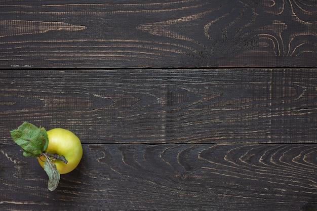 천연 갈색 나무 배경에 잎이 달린 신선한 유기농 노란색 사과