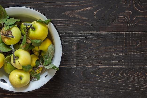 자연 갈색 나무 배경에 철 그릇에 신선한 유기농 노란 사과와 녹색 배