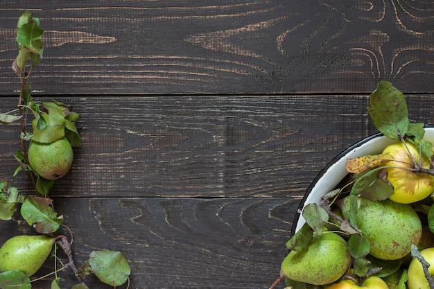 자연 갈색 나무 배경에 철 그릇에 신선한 유기농 노란색 사과와 녹색 배