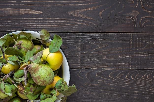 자연 갈색 나무 벽에 철 그릇에 신선한 유기농 노란 사과와 녹색 배