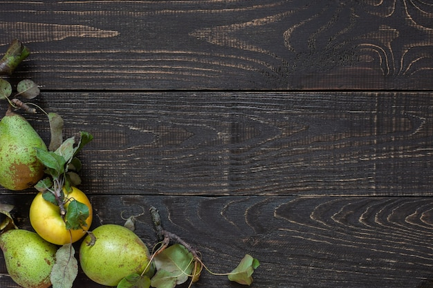 천연 갈색 나무 배경에 잎이 달린 신선한 유기농 노란색 사과와 녹색 배