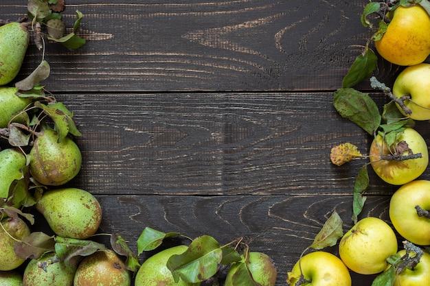 자연 갈색 나무 벽에 잎을 가진 신선한 유기농 노란 사과와 녹색 배