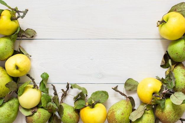자연적인 흰색 나무 배경에 잎이 있는 신선한 유기농 노란색 사과와 녹색 배