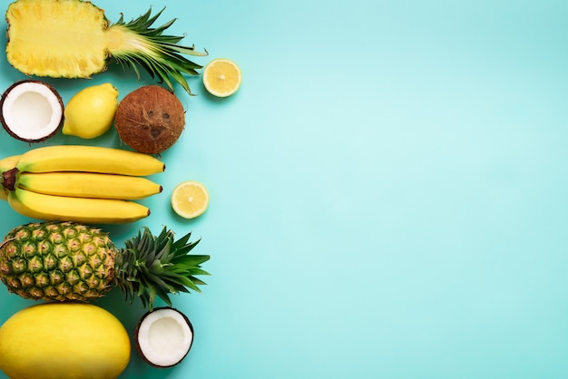 Fresh organic yellow fruits over blue background. monochrome concept with banana, coconut, pineapple, lemon, melon.