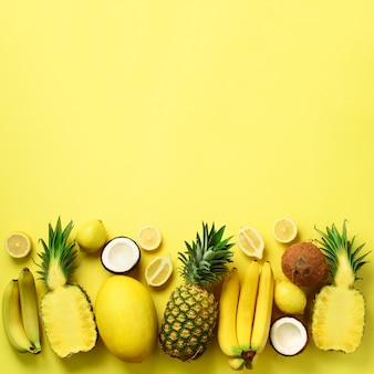 Fresh organic yellow fruits over sunny background. monochrome concept with banana, coconut, pineapple, lemon, melon.