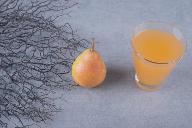 Pera gialla organica fresca con un bicchiere di succo