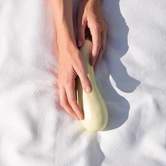 白い背景の上の女性の手で新鮮な有機ズッキーニ。選択の概念