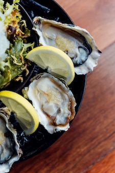 Fresh oysters close-up on black plate, served table with oysters, lemon, ice and salad.