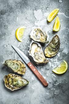 氷、ナイフ、レモンウェッジの新鮮なカキ。素朴な石の背景。生牡蠣を開封しました。