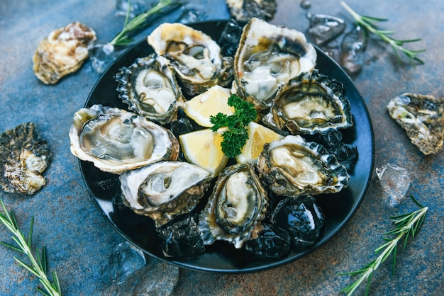 Fresh oysters seafood on a black plate. open oyster shell with herb spices lemon rosemary served table and ice healthy sea food raw oyster dinner in the restaurant gourmet food
