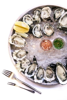Fresh oysters served on ice in steel plate with sliced of lemon and spicy sauces