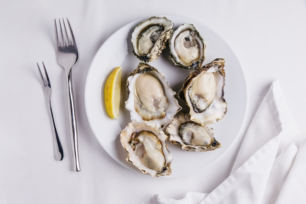 Fresh oysters served in white plate with sliced of lemon on white tablecloth