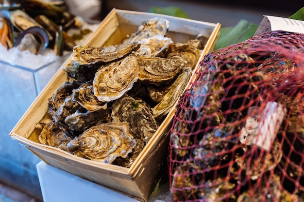 Fresh oysters in shell in wooden box and net in buffet line.