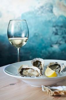 新鮮な牡蠣のプレートにレモン、木製のテーブルにグラスワイン