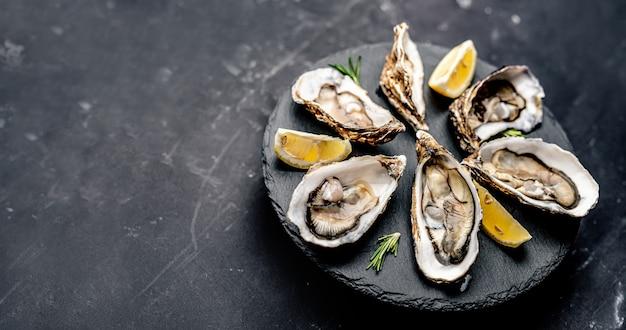レモンと新鮮な牡蠣は、黒い表面に分離された丸い大皿で提供