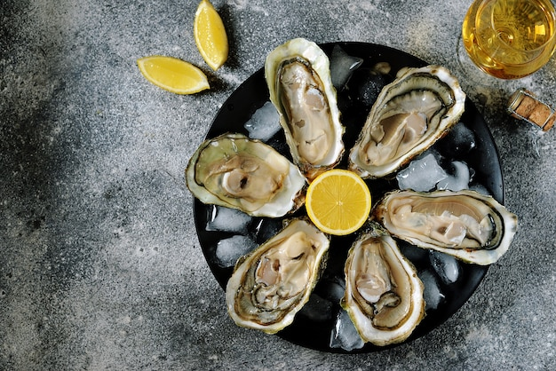 Fresh oysters with lemon slices on a plate
