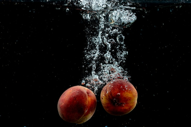 Fresh pair of peaches in the water