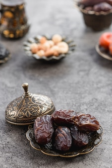 Fresh palm dates on the bronze plate with lid on concrete plate