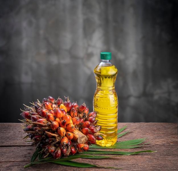 Свежие фрукты пальмового масла и растительное пальмовое масло на пальмовых листьях в деревянных фоне.
