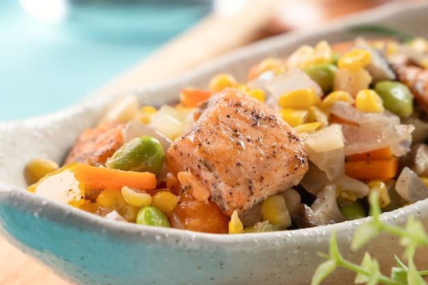青い木製のテーブルに枝豆、にんじん、玉ねぎ、きのこ、とうもろこしの穀粒などの野菜炒めを添えた新鮮なサーモンキューブチョップの炒め物