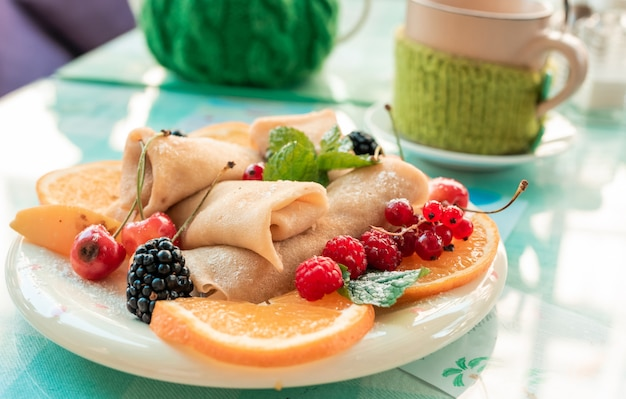 果実と新鮮なパンケーキ。茶色のプレートに森の果実の果実とパンケーキ。ブルーベリー、ラズベリー、チェリー、スグリ、オレンジ、ミントの葉がパンケーキに飾られています。トップビュー食品写真