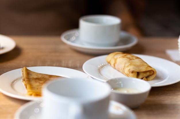 Свежие блины с начинкой на столе рядом с белыми кружками для кофе или чая на завтрак. блины на сладкий десерт после обеда в уютном кофе.