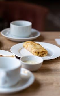 아침 식사로 커피나 차를 마실 수 있는 흰색 머그잔 옆 테이블에 채워진 신선한 팬케이크. 점심 식사 후 아늑한 커피와 함께 달콤한 디저트를 위한 팬케이크.