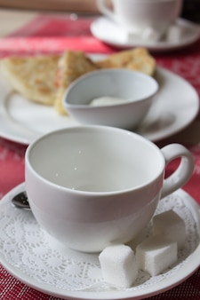 朝食用のコーヒーまたは紅茶用の白いマグカップの横にあるテーブルに詰め物が入った新鮮なパンケーキ