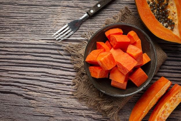 Свежую папайю нарезать кусочками, выложить на черную тарелку.