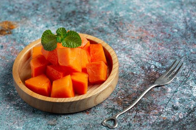 Свежую папайю нарезать кусочками, выложить на деревянную тарелку.